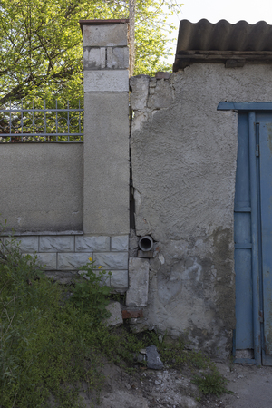 Water drain in the wall. There are a stone fence and an old atone structure.