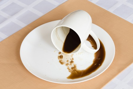 Overturned cup with the coffee. Close-up on the placemat. A white tablecloth used as a background.