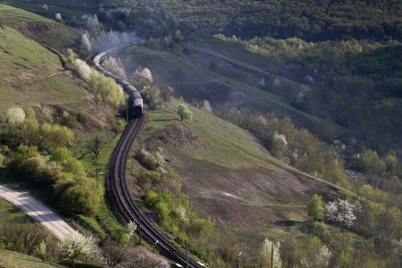 Moving passenger train. The train with smoke goes through the field and the village. Stock Photo