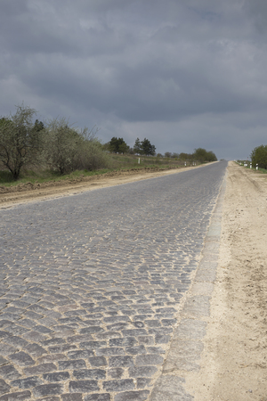 Old cobblestone road. The road going into the clouds.