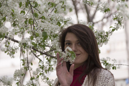 Charming young woman in white cardigan. Shooting has been in the spring city within the Roses Valley Park.