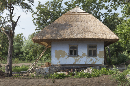 Traditional moldovian rural house. House is under roofing from bulrush and an old pear. Stock Photo