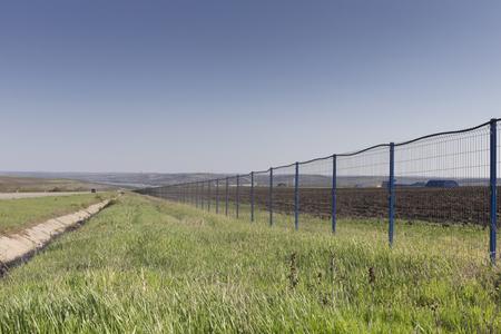 Beautifu spring landscape and a modern metal fence. A farm enterprise in Moldova.