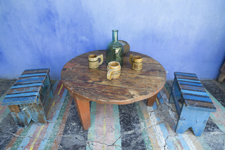 Moldavian still life. The blue lime wall. There are traditional wooden mugs and a blue glass bottle. Stock Photo