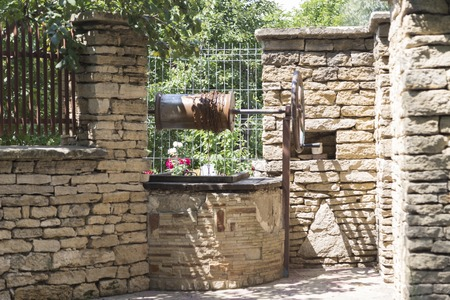 Traditional draw well in the street of a village. The well is made of limestone stones.