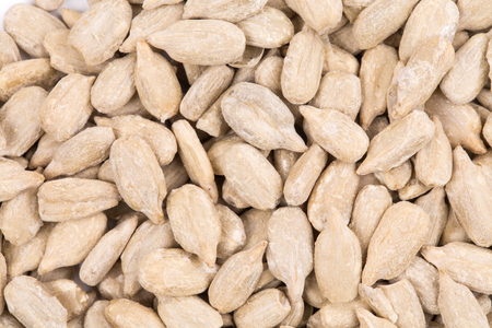 A large number of purified sunflower grains as a background. Close-up.