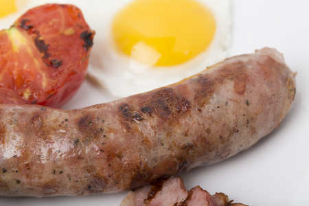 Fragment of english breakfast with the sausage. Close-up.