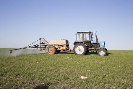 Farmer on a tractor is spraying green wheat field. Beautiful views of Moldova. Standard-Bild - 115009527