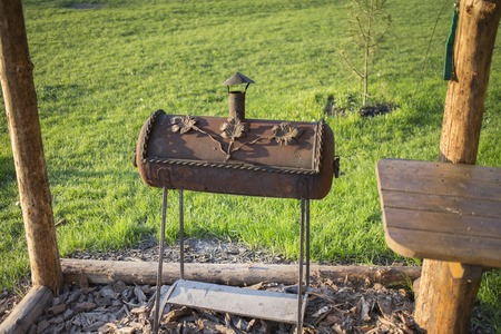 The grill with your hands from the gas cylinder. It is located in the back yard.