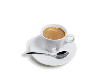 A cup of coffee on a saucer and with spoon. This is isolated in a white background. Close-up.