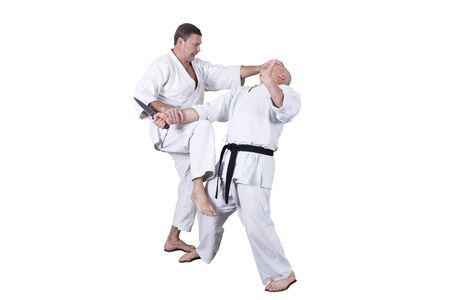 Adult athlete performs formal goju-ryu exercises isolated in a white