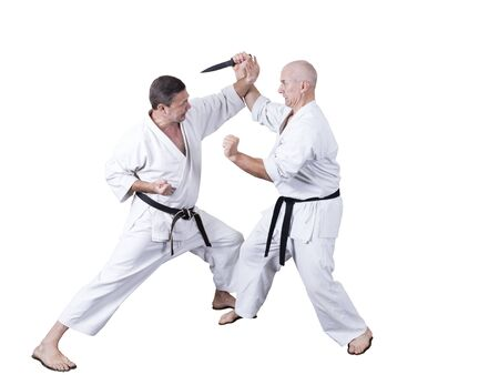 Adult athlete performs formal goju-ryu exercises isolated in a white Stock fotó