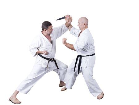 Erwachsener Athlet führt formelle Goju-Ryu-Übungen durch, die in einem Weiß isoliert sind Standard-Bild
