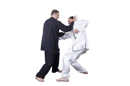 Adult athlete performs formal goju-ryu exercises. It is isolated in a white background. Close-up.