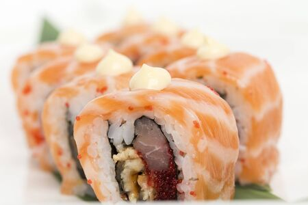 Original sushi roll fusion with various fillings. It is located in a white background. Close-up.