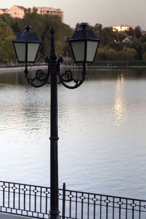 A darkened vintage style street light on the lake. This is photographed during sunset.
