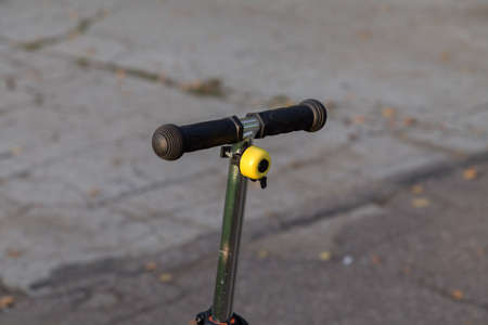 Yellow bike bell on the handlebars of the scooter. Close-up.