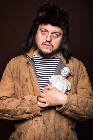 lenin: Sad russian holding Lenin sculpture