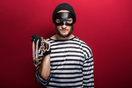 furtive: A thief holding stolen necklace