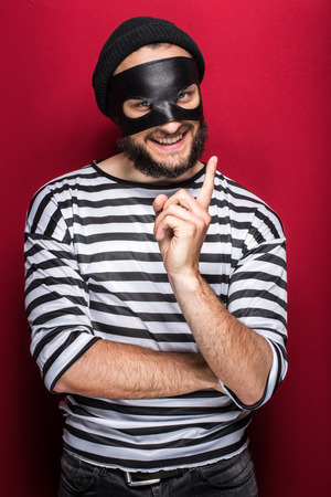 furtive: Crafty bandit smiling and threaten with finger on red background