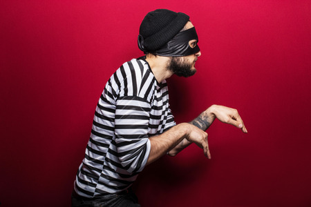 A thief with mask slinking on red background   스톡 콘텐츠
