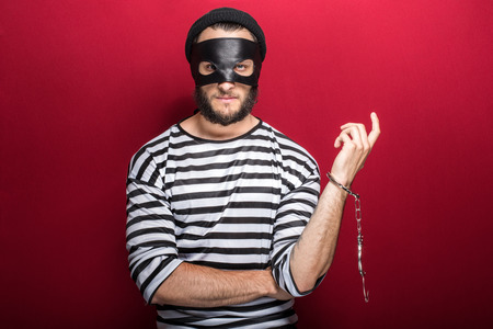furtive: Thief arrested as a consequence of his crime  Portrait on red background