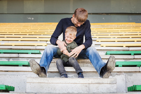 family tickle: Father and son playing in empty stadium