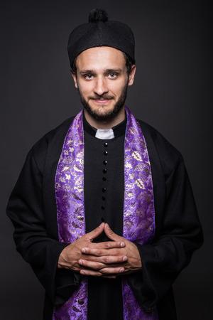 Portrait  young smiling priest  Studio portrait on black background   photo
