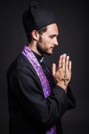Praying priest  Studio portrait on black background   photo