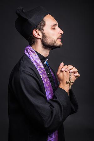 Young priest praying  Studio portrait on black background   photo