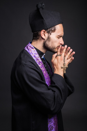 priesthood: Young catholic priest praying  Studio portrait on black background