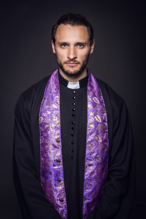 Portrait of young priest. Studio portrait on black background