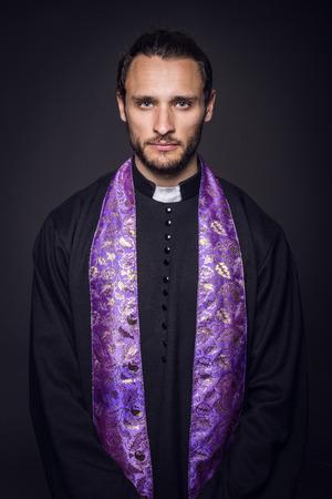 Portrait of young priest. Studio portrait on black background   photo