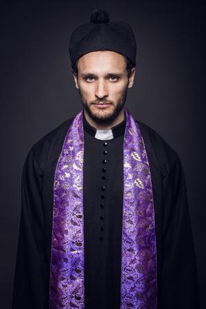 Portrait of young pastor. Studio portrait on black background   photo