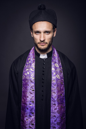 sotana: Retrato de joven pastor. Retrato de estudio sobre fondo negro