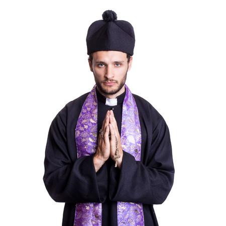 Young catholic priest praying. Studio portrait isolated on white background photo