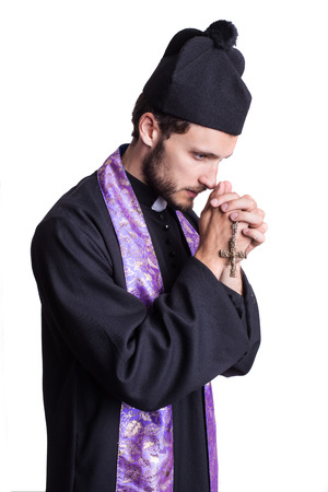vicar: Christian priest praying. Studio portrait isolated on white background Stock Photo