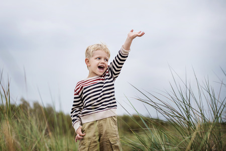 ��beautiful boy�: excited beautiful boy puts up his hand and screaming. Oudoor portrait  Stock Photo