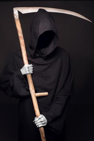Dood met zeis staande in het donker. Studio portret op zwarte achtergrond