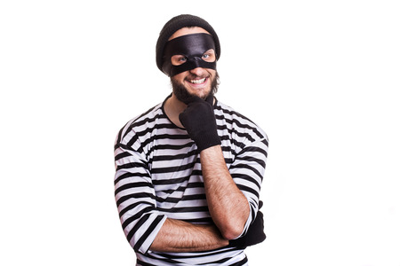 attacker: Crafty criminal smiling and thinking. Portrait isolated on white background