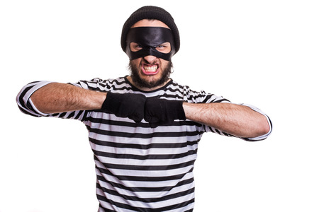 furtive: Portrait of a angry thief threaten with a fist. Isolated on white background