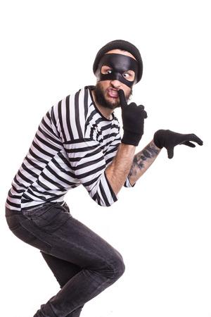 Een dief met een masker stilletjes sluipen. Portret geïsoleerd op een witte achtergrond Stockfoto