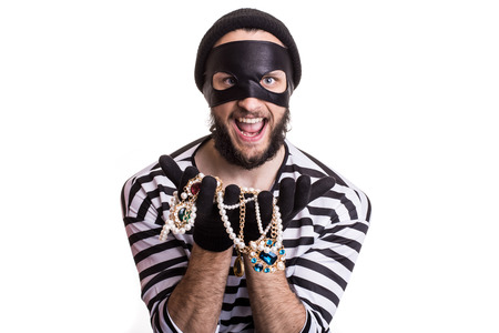 Bandit showing stolen jewelry and smiling. Portrait isolated on white background 스톡 콘텐츠