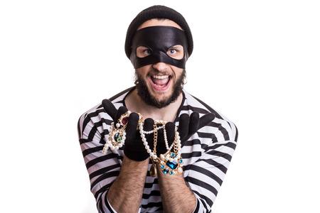 Bandit tonen gestolen sieraden en glimlachen. Portret geïsoleerd op een witte achtergrond Stockfoto