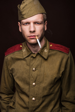Russian soldier smoking cigarette. Studio portrait isolated on brown background photo
