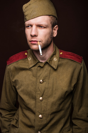 Second world war russian soldier smoking cigarette and looks at something. Studio portrait isolated on brown background photo