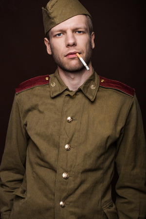Second world war russian soldier smoking cigarette. Studio portrait isolated on brown background photo