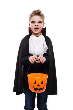 Cute boy dressed as a vampire for Halloween and holding a pumpkin basket isolated over white background 스톡 콘텐츠