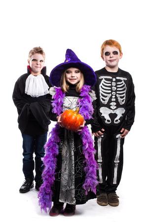 Een klein meisje en twee jongens gekleed in Halloween kostuums: heks, skelet, vampier. Studio portret geïsoleerd op witte achtergrond