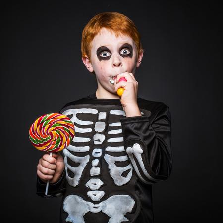 Gelukkig jonge rood haar jongen met skelet kostuum bedrijf en het eten van kleurrijke snoepjes. Studio portret op zwarte achtergrond